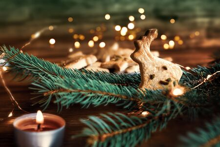 Christmas cookies and candle with festive lights on rustic wood