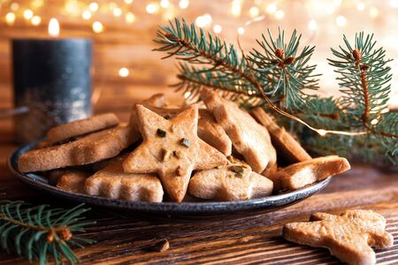 Tasty homemade christmas cookies with festive golden lights on rustic wood