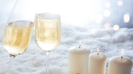 Candles and champagne with festive bokeh in cold snowy winter for a new year background