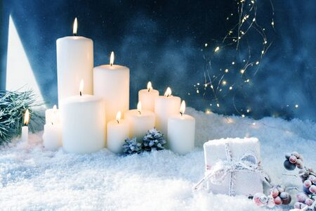Christmas decoration with burning candles in a dark blue winter night