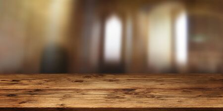 Empty wood table surface in front of gloomy room with short depth of field for a background