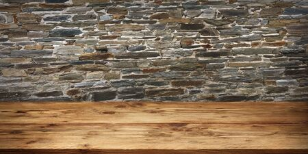 Empty wood table surface in front of old rustic stone wall for a product presentation