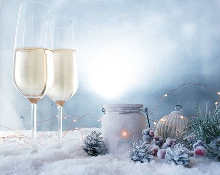 Winter still life with champagne and christmas ornaments in snow