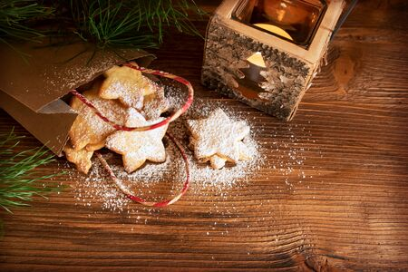 Christmas decoration and homemade cookies with powder sugar on rustic wooden table for a background