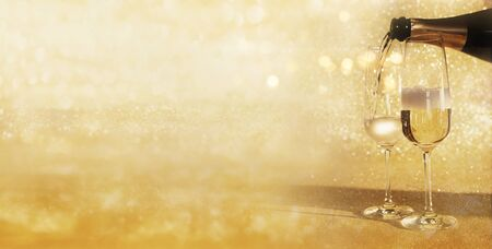 Pouring champagne on golden glittering background for a luxury concept