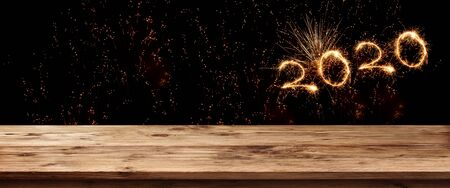 Gold sparkling new year 2020 on night sky. Background with empty wooden surface and fireworks for a concept decoration and space for text.