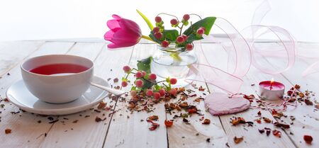 Cup of tea on mothers day with aromatic fruit tea. Floral decoration with pink heart on white vintage wooden table.