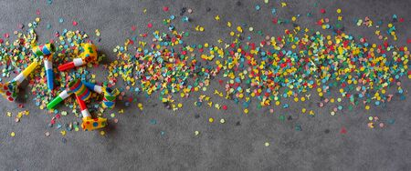 Flat lay photography with colorful carnival accessories. Confetti and streamers on gray background. Top view for mardi gras celebration and birthday with space for text.