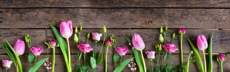 Pink tulips on old rustic wood. Fresh spring flowers decorated in a row for mothersday. Wide photography for a background with space for text. Top view, flat lay. Banque d'images - 142148411