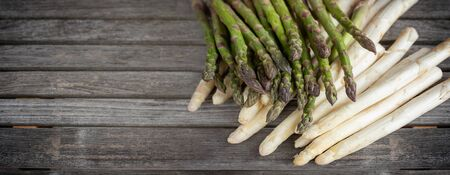 Bunch white and green asparagus on old wood. Horizontal close-up of fresh vegetables for a healthy nutrition concept. Space for text.
