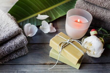 Natural olive soaps with a scented candle and bath accessories in a romantic setting for a wellness concept. Spa still life on gray wooden background with short depth of field and space for text.