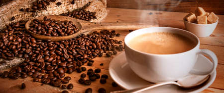 Fragrant coffee beans with a cup of fresh coffee on an old rustic wooden table. Horizontal coffee still life for a barista concept. Close-up.