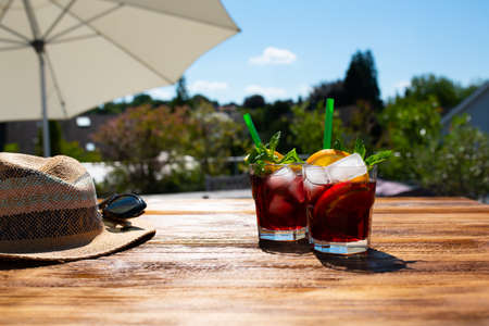 Fresh cold summer drink on sunny terrace with parasol and straw hat on wooden table. Background for vacation and leisure. Short depth of field.