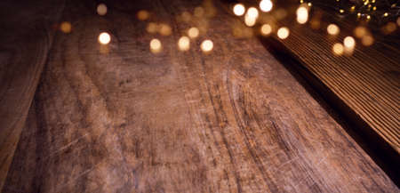 Golden christmas bokeh lights on aged wooden table. Background with blurred lights for your christmas decorations. Space for text. Archivio Fotografico