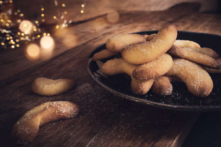 Delicious christmas pastries on a plate. Vanilla crescents with sugar on rustic wooden table with golden bokeh. Atmospheric still life with a short depth of field. 写真素材 - 157190228