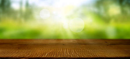 Blurred spring landscape with shining bokeh and empty wooden table. Sunny background with space for decoration and text. Stockfoto