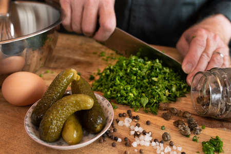 Preparing a gribiche sauce for green asparagus. Hands prepare fresh ingredients for a tasty side dish. Gastronomy and lifestyle background. Close up with short depth of field.