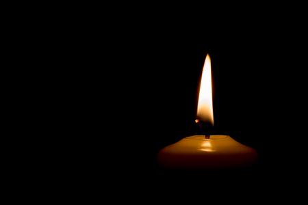 christmas objects: Burning candle isolated on black background. Stock Photo