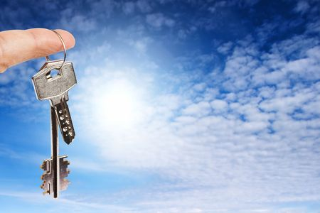 homebuyer: Finger with key on blue sky background Stock Photo