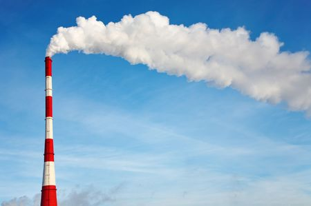 polluting: Air polluting smokestack against blue sky  Stock Photo
