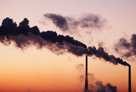 Air polluting smokestack against sunset sky photo