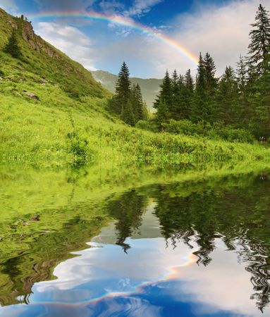 mirror on the water: Landscape with forest and rainbow