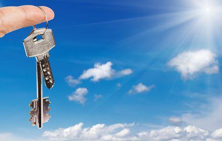 homebuyer: Finger with key against blue sky backgroundr
