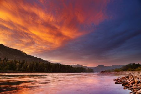 Mountain landscape with river and colorful sky photo