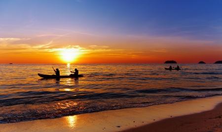 Mar con kayakers en la puesta del sol, isla de Chang, Tailandia