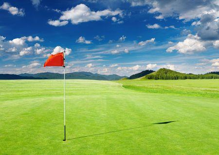 ゴルフ場の穴に赤い旗を持つ