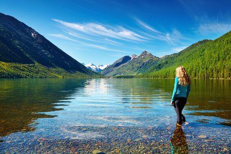 Paisaje de montaña con la chica de pie en el lago