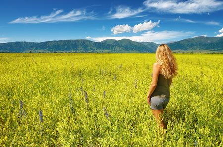 Blond girl standing in blooming yellow field Stock Photo