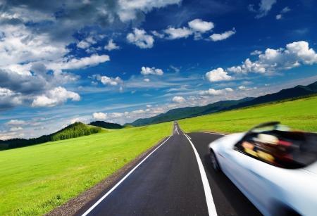 空の道路にぼかしモーションのスポーツカー