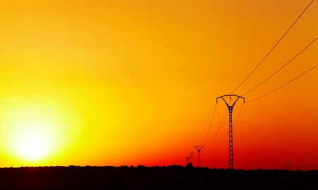 Electric power line in Sahara Desert against colorful sky at sunset  photo