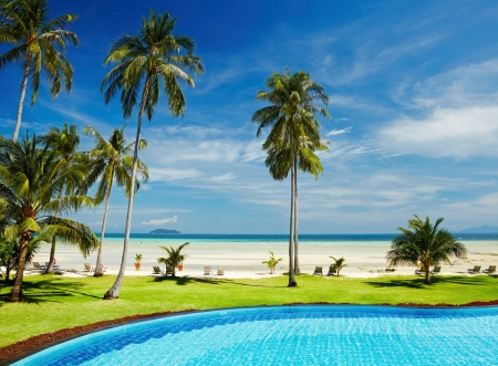 Tropical beach with coconut palms and swimming pool