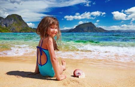 Small girl sitting on the sand, El-Nido, Philippines Stock Photo - 17699314