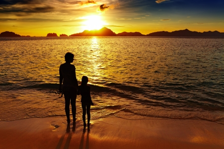 Mother and daughter on the beach at sunset, El-Nido, Philippines