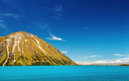 ターコイズ ブルーの湖と青空のある風景します。
