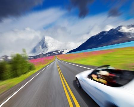 道路とモーションのスポーツカーと山の風景をぼかし 写真素材