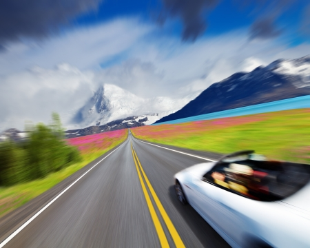 Mountain landscape with road and sports car in motion blur photo