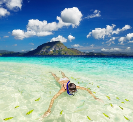 Tropical beach, woman swimming with snorkel photo