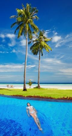 palmtree: Woman in swimming pool at tropical beach