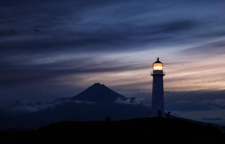 Cape Egmont Lighthouse and Taranaki Mount on background, New Zealand photo