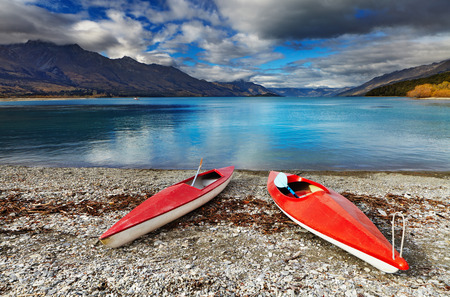 Red kayaks at the lakeside, Wakatipu Lake, New Zealand Imagens