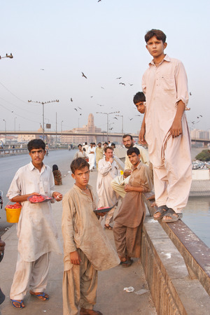 netty: KARACHI, PAKISTAN - NOV 14: Boys on the Netty Jetty Bridge sell offal for kite feeding on november 14, 2006 in Karachi, Pakistan. Kite feeding is favorite fun of local people