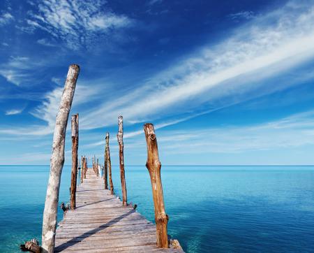 Landschap: Houten pier op een tropisch eiland, de zee en de blauwe hemel in Thailand Stockfoto