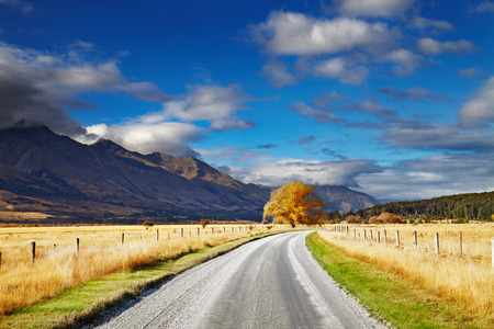 south island new zealand: Mountain landscape with road and blue sky, Otago, New Zealand Stock Photo