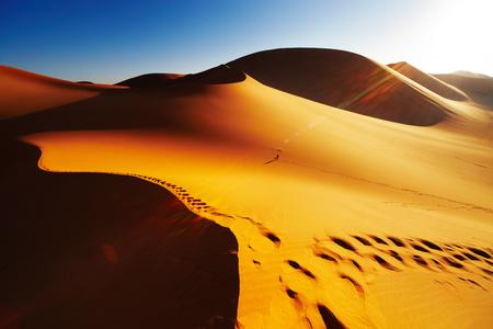Zandduin met voet afdrukken bij zons opgang, Sahara woestijn, Algeria Stockfoto