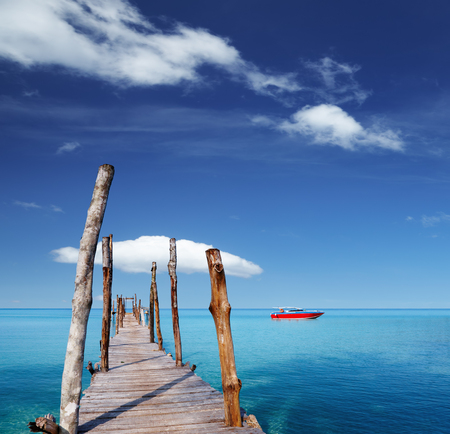 Wooden pier on a tropical island, sea and blue sky