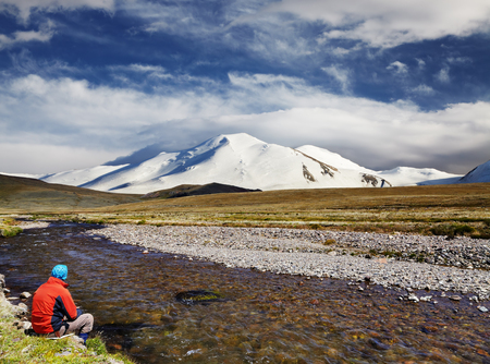 Man sitting alone on the river bank against snowy mountain and blue sky background, travel concept